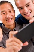 Close-up Of Two Smiling Friends Taking Self Portrait With Cell Phone