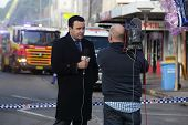 News Correspondent Delivers A News Bulletin On Site Of Shop Blast