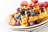 Waffles with berries and honey on table