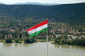 stock photo of hungarian  - The hungarian flag with beautiful landscape background - JPG