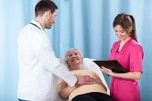 picture of geriatric  - Horizontal view of young doctors talking with geriatric patient - JPG