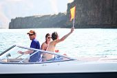 stock photo of ski boat  - a bunch of people on a boat with one waving a flag indicating a water skier in the water - JPG