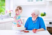 Grandmother Baking Cake With Granddaughter