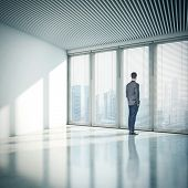Businessman Standing In Office And Looking At City