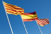 Flags Of Spain, Catalonia And Tarragona City Above Blue Sky