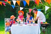 picture of holland flag  - Happy big Dutch family with kids celebrating a national holiday or sport victory having fun at a grill party in a garden decorated with flags of Netherlands screaming Hup Holland - JPG