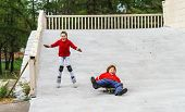 Group Of Children Rollerskating In Public Park