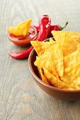 Tasty nachos, red tomatoes and chili pepper in color bowl on wooden background
