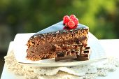Chocolate cake with fresh berries on plate, on wooden table, on bright background