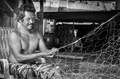 Thai fishermen mending his fishing net