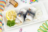 pickled herring fillet and garnish on a plate, party decoration and champagne cork