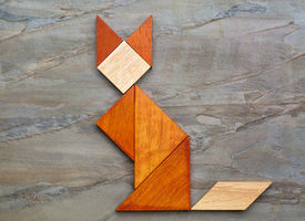 stock photo of tangram  - abstract picture of a cat built from seven tangram wooden pieces against slate rock background - JPG