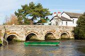 River Avon Christchurch Dorset England UK with bridge and green boat