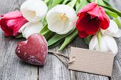 Bouquet of tulips with an empty tag and red heart on wooden background