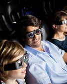 Smiling man watching 3D movie with family in cinema theater