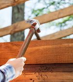 Cropped image of female worker's hand hammering nail on timber frame at site