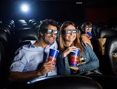 Happy mid adult couple having drinks while watching 3D movie in cinema theater
