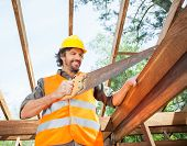 Happy male construction worker cutting wood with handsaw at site