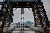 Manhattan New York cloudy skyline from East River floodgates structure USA