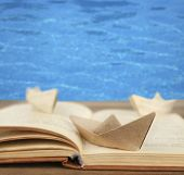 Origami boats on old book on sea background