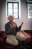 Senior Arabic Pakistani man praying in mosque