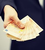 picture of man in suit with euro cash money.