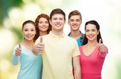 friendship, ecology, gesture and people concept - group of smiling teenagers showing thumbs up over green background