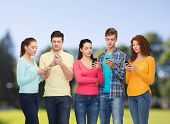 friendship, technology and people concept - group of serious teenagers with smartphones over park background