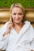 people, beauty, lifestyle, technology and relaxation concept - beautiful young woman in white bath robe with smartphone calling and talking at spa