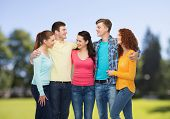 friendship, summer vacation, nature and people concept - group of smiling teenagers standing and embracing over green park background