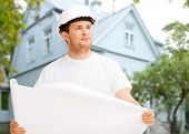renovation, building, people and home concept - male builder or architect in helmet holding blueprint over living house background