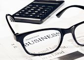 Business Word See Through Glasses Lens On Financial Newspaper Near Calculator