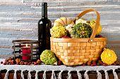 Many Pumpkins In Wicker Basket With Bottle Of Red Wine.