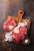 Raw Fresh Cross Cut Veal Shank And Ingredients For Making Osso Buco On Wooden Cutting Board On Dark