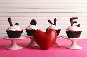 Delicious Valentine Day cupcakes on wooden background