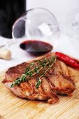 Steak with herbs on wooden stand and wine on table close up