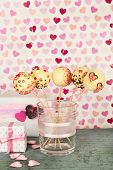 Tasty cake pops and gifts on color background