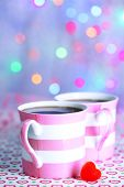 Two cups on table on lights background