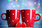 Two red cups on table on lights background