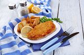 Breaded fried fish fillet and potatoes with asparagus and sliced lemon on plate with napkin on color wooden planks background