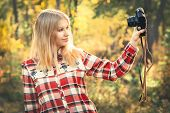 Young Woman wearing plaid shirt with retro photo camera taking selfie shot outdoor