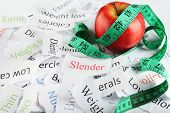 Papers with different words, apple and measuring tape close up
