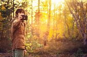 stock photo of swag  - Young Man with retro photo camera outdoor hipster Lifestyle forest nature on background - JPG