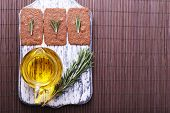 Crispbread with sprigs of rosemary on wooden cutting board with jug of oil on bamboo mat background