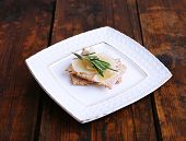 Crispbread with slices of Parmesan cheese with sprig of rosemary on plate on wooden table background