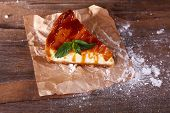 Cheese cake with sugar powder on paper on wooden background