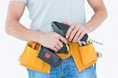 Cropped image of repairman holding handheld drill over white background
