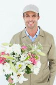 Portrait of happy delivery man holding bouquet against white background