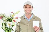 Portrait of happy delivery man with bouquet showing blank note against white background
