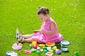 Toddler kid girl playing with food toys sitting in green turf grass garden
